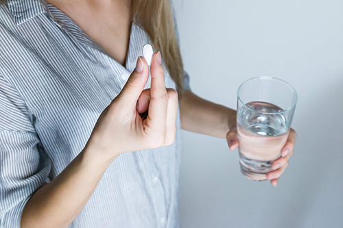 A woman holds a pill and a glass of water